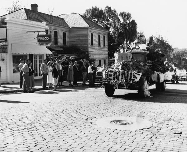 "A decorated pickup truck with the name ""Jennie"" on the front carrying several women dressed in Seminole-inspired costumes makes its way up the street passing the Capitol Radio Labs during the 1948 Florida State University Homecoming parade, as spectators in formal wear watch."