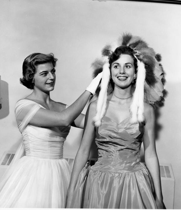 1955 Homecoming queen Margaret Ann Ballinger shown crowning 1956 Queen Laytie Brown with the traditional headdress, both in formal wear.