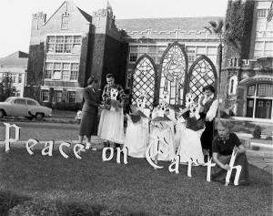 Four unidentified students setting up outdoor Christmas decorations in front of the Westcott Building during the 1950s.