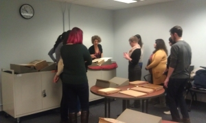 """(Photo credit: Rebecca Bramlett) Prof. Stephanie Leitch and her graduate Renaissance Observation class examining a copy of Sebastian Munster's """"Cosmographia,"""" published in 1550"""