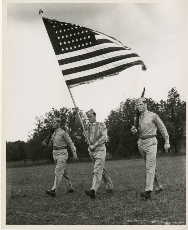 ROTC members in the 1960s with the American flag.