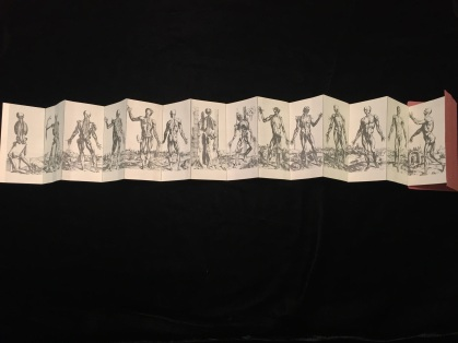 Accordion-fold pages allow you to see that the background of the figures forms one continuous landscape.