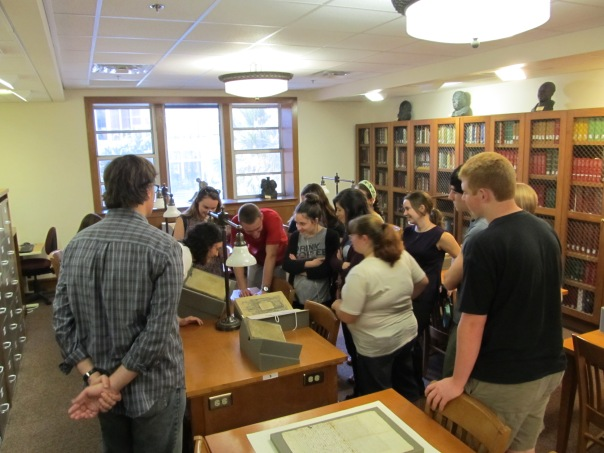 Rory Grennan looks on as Kat Hoarn closely examines a rare book with the FSU History Club.