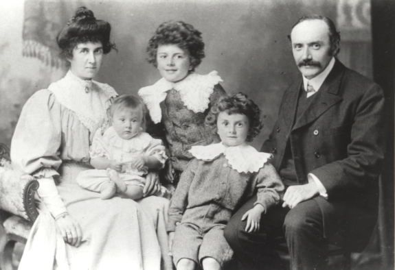 An formal portrait of the Dirac family with Florence on the left and Charles on the right. Infant Betty, Felix, and Paul are situated between them.