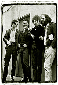 A black and white photograph of four men against the backdrop of a wall and a door. The photo style is relaxed and candid.