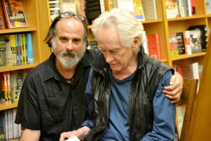 Two men seated in a bookstore. One, Michael Rothenberg, has his arm around the other, Michael McClure. Rothenberg looks directly at the camera while McClure is examining a book in his lap.