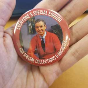 "Hand holding a pinback button that features Mr. Rogers and reads ""Everyone's Special Enough for Special Collections & Archives"""