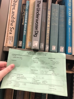Archives pull-slip held up against its corresponding book
