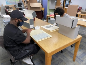 Two people sitting at a desk looking at Special Collections & Archives materials